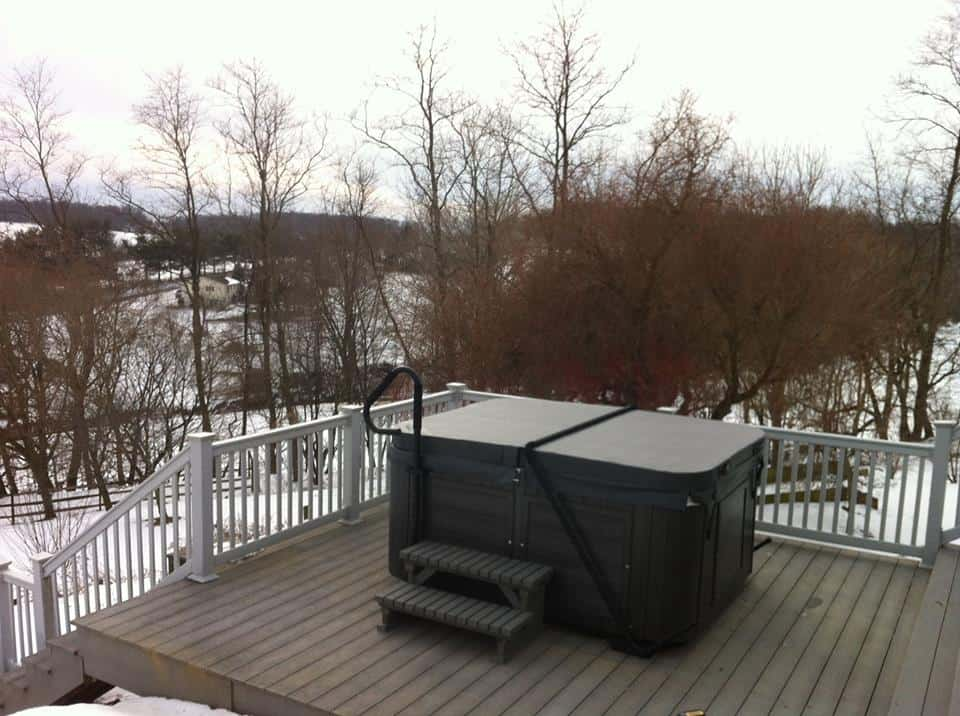 Covered Arctic Spas Hot tub in the backyard in winter