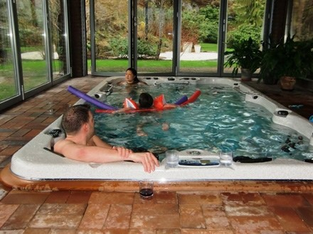family having fun in an arctic spas swimspa inside a house